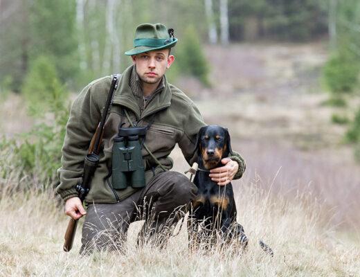 jaeger mit waffe und fernglas kniet neben seinem Jagdhund